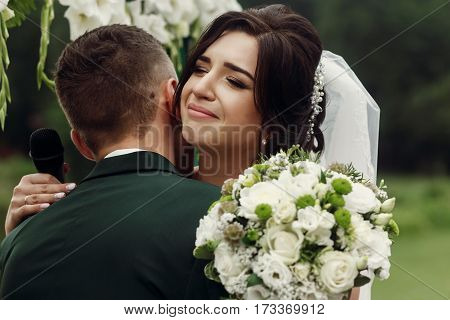 Gorgeous Emotional Bride In Stylish White Wedding Dress With Bouquet Hugging Handsome Groom During O