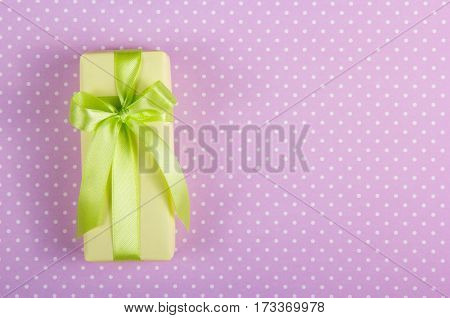 Gift box with a bow on a background of polka dots. Copy space