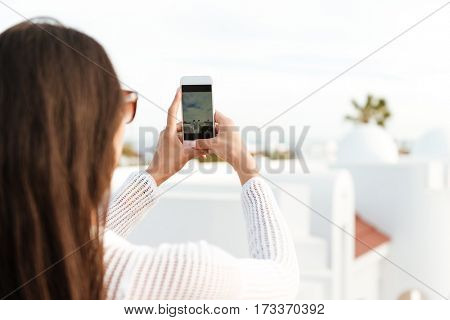 Back view of Brunette woman in white clothes which making photo on the phone