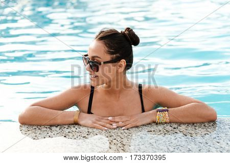 Close-up view of Woman which swimming in pool and looking away
