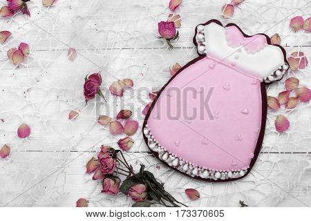 Cookies With Glaze In The Form Of Dress With Petals Of Dried Roses. On White Wooden Surface.