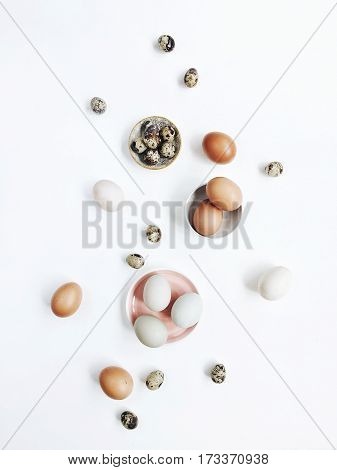 White and brown Easter eggs and quail eggs on white background. Flat lay, top view. Traditional spring concept.