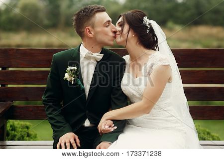Cute Newlywed Couple Sitting On A Bench In The Park, Smiling Handsome Groom In Stylish Suit Kissing