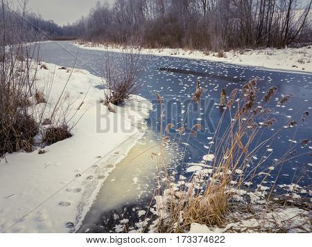 Winter landscape with river covered with ice and frost.