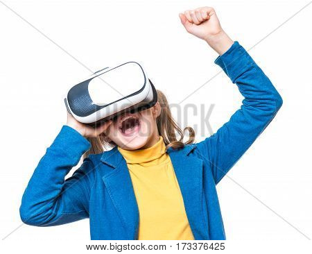 Happy little winner girl wearing virtual reality goggles watching movies or playing video games, isolated on white background. Victory screaming cheerful child looking in VR glasses and gesturing with his hands.