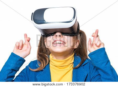 Happy little girl wearing virtual reality goggles watching movies or playing video games, isolated on white background. Cheerful smiling kid looking in VR glasses and making luck gesture. Child experiencing virtual reality.