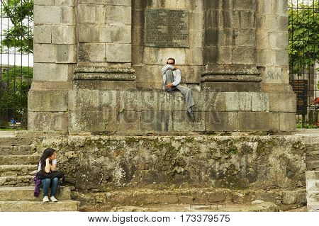CARTAGO, COSTA RICA - JUNE 17, 2012: Unidentified people sit at the entrance to the ruins of the Santiago Apostol cathedral in Cartago Costa, Rica.