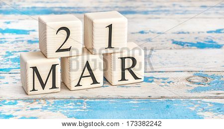 March 21st. Wooden cubes with date of 21 March on old blue wooden background.