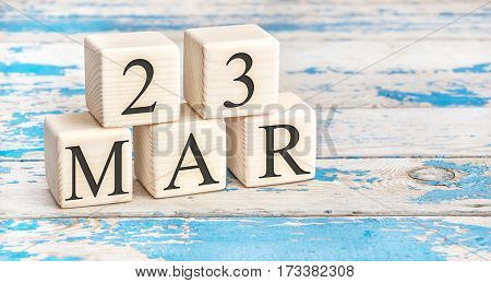 March 23th. Wooden cubes with date of 23 March on old blue wooden background.