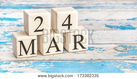 March 24th. Wooden cubes with date of 24 March on old blue wooden background.