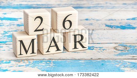 March 26th. Wooden cubes with date of 26 March on old blue wooden background.