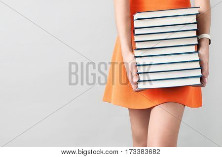 The Girl In Orange Dress Holding A Stack Of Books