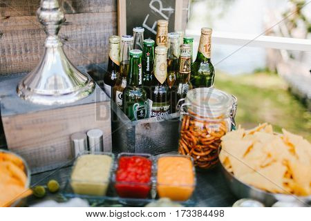 Different brands of beer bottles with snacks