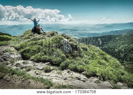 Woman hiking in mountains at sunny day time.