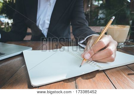 Business woman write on notebook and use laptop working outdoor in coffee shop vintage tone.