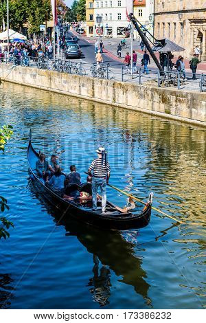 BAMBERG, GERMANY - Circa September, 2016: Tourists in a gondola on the Regnitz River in Bamberg, Bavaria, Germany in the area known as Little Venice for its quaint fisherman cottages