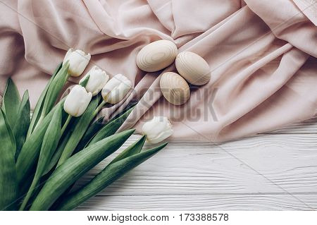 Stylish White Tulips And Simple Easter Eggs On Rustic Wooden Background And Fabric Flat Lay. Happy E
