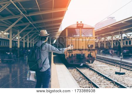 Young man traveler with sky blue backpack and hat showing thumbs up with train background at train station Bangkok. Traveling in Bangkok Thailand. Travel concept