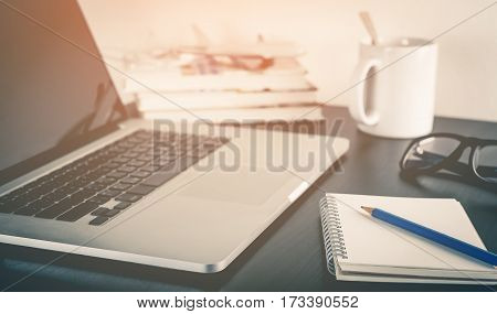 Computer on office table with morning coffee and notebook