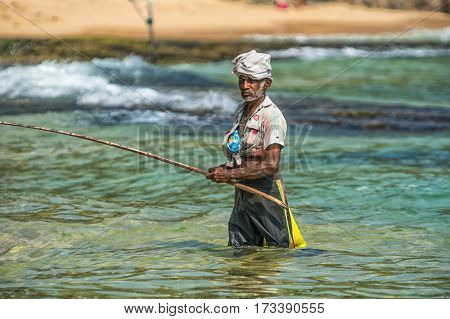 Weligama, Sri Lanka -  January 18, 2017:  Portrait Of Local Fisherman Sitting On Boat. Tourism And F