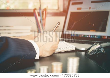 Stock trader is checking the graph and writing down plan on notebook