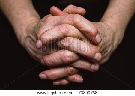 Old hands of senior woman clasped together