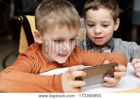 Two boys playing in smartphone in cafe