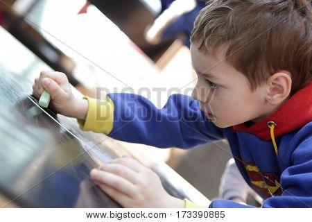 Child draws a chalk on a blackboard