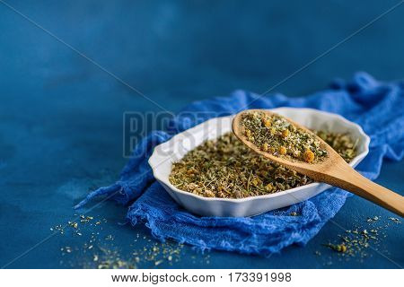 Dried chamomile or camomile flowers on a blue background
