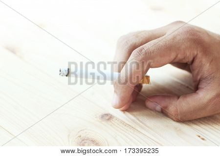 Male Hand Holding A Cigarette On Wooden Background