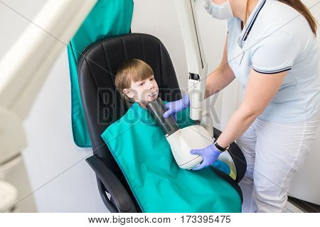 child sits in the office of the radiologist. The doctor does an x-ray of the child.