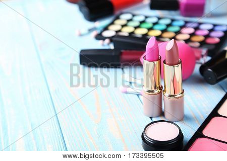 Different Makeup Cosmetics On Blue Wooden Table