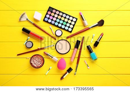 Different Makeup Cosmetics On Yellow Wooden Table