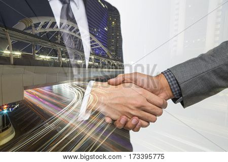 Double exposure of Business handshake. Business hands shake and business people concept. Two men shaking hands on bangkok city background. Partnership Deal
