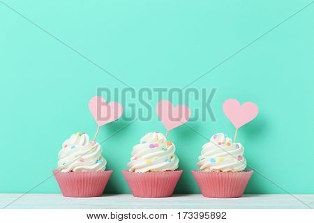 Tasty cupcakes on a green background, close up