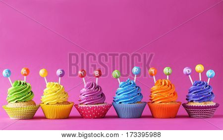 Tasty cupcakes on a pink background, close up