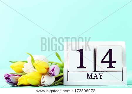 Bouquet of tulips with cube calendar on mint wooden table