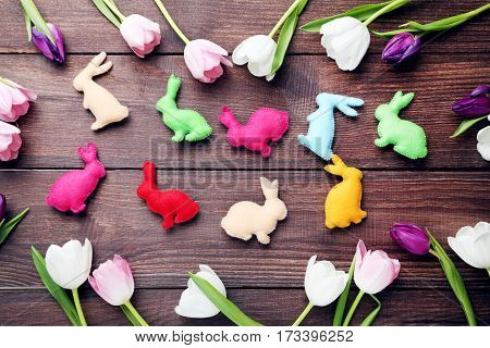 Bouquet Of Tulips With Handmade Easter Rabbits On Brown Wooden Table