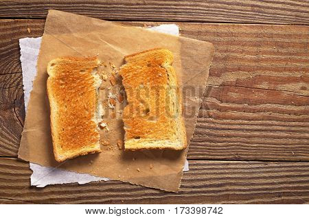 Two half toasted bread on old wooden table top view. Space for text