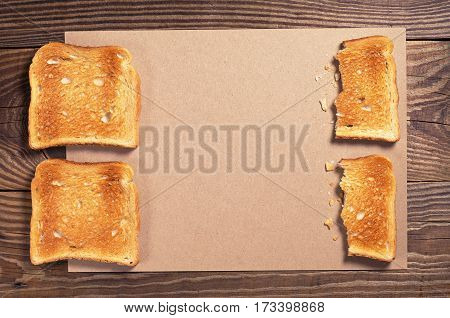 Slices of toasted bread and blank paper on old wooden table top view. Space for text