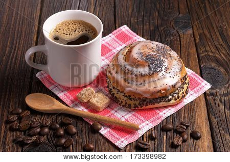 Cup of coffee and fresh sweet bun with poppy seeds on dark wooden table