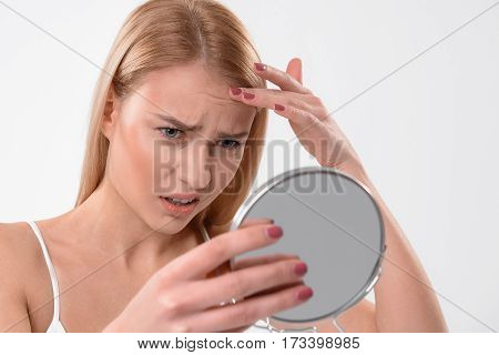 Aging is inevitable. Frustrated young woman is looking at mirror while touching her wrinkles on forehead. Isolated on background