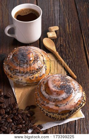 Two sweet buns with poppy seeds and cup of coffee on dark wooden table