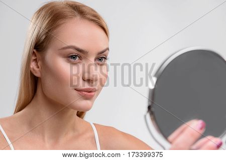 I like my skin. Cheerful young girl is standing and looking at mirror with confidence. Isolated