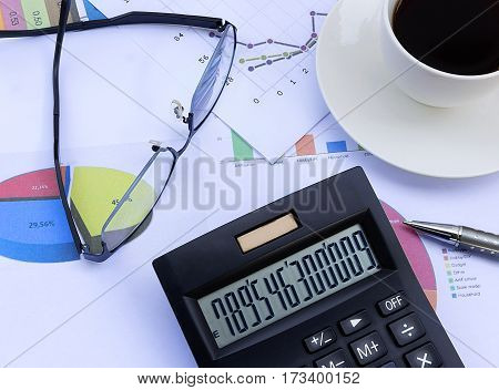 calculator glasses pen coffee cup and financial chart business work station with paperwork is on the desk finance and business concept