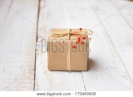 Gift box wrapped in craft paper tied with twine tender small red flower white plank wood background minimalistic copyspace kinfolk