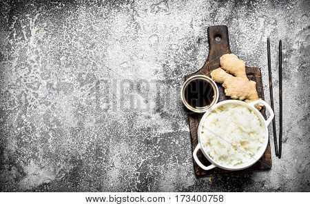 Asian Food. Boiled Rice With Soy Sauce On The Old Board. On Rustic Background.