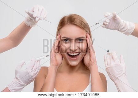 I will be young forever. Happy young woman is touching her head and laughing. Doctors hands holding syringes with botox near her face. Isolated