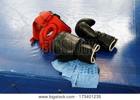 Two black leather boxing gloves red protective headgear and blue towel lies on the edge of the boxing ring