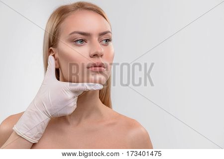 Hands of beautician examining facial proportion of young woman before operation. Patient is standing and looking side with serenity. Isolated and copy space in right side